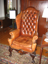 Rococo style mahogany styled wing-back chair with brown leather upholstery and tufted back with riveted edges.