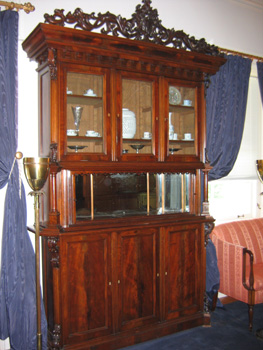 An imposing mahogany wood breakfront /display cabinet circa 1870 in a heavy Rococo style.