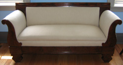 Empire settee with ivory upholstery; mahogany and veneered wood, straight top, curved arms, circa 1860.